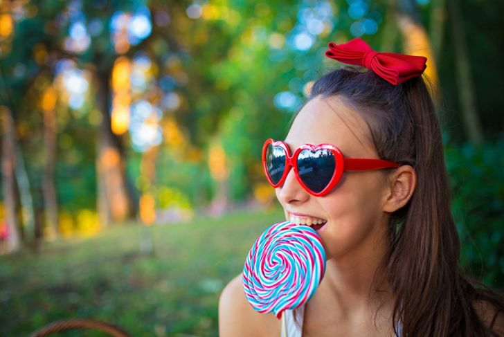 A woman with a large lollipop wearing a bow hair clip