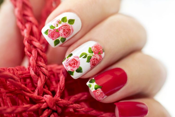 A red and white manicure with realistic rose print