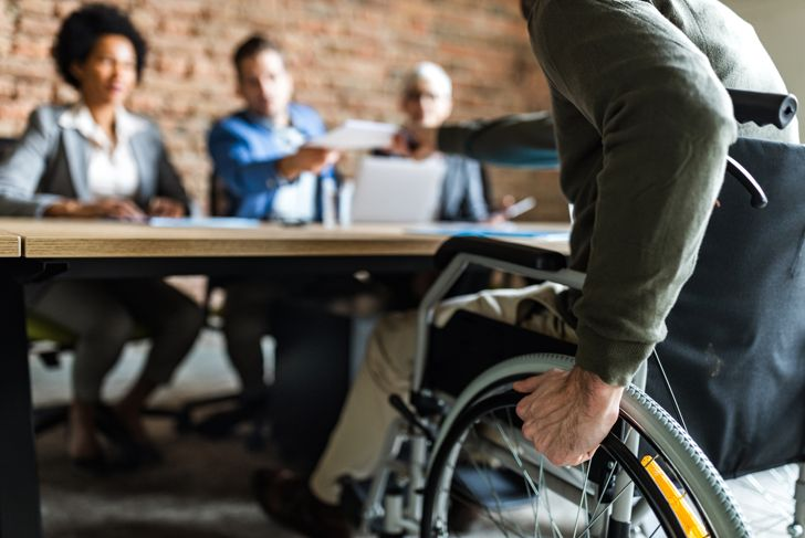 Close up of unrecognizable candidate in a wheelchair on a job interview in the office.
