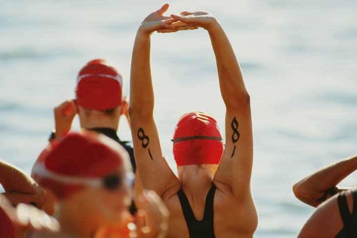 Triathletes stretching before swimming leg of race (rear view)