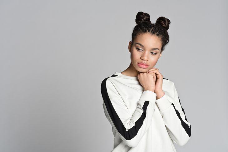 Studio portrait of pensive afro american cute teenage woman. Studio shot, grey background.