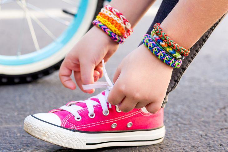 Young girl wearing loom bracelets, lacing sneakers. Y