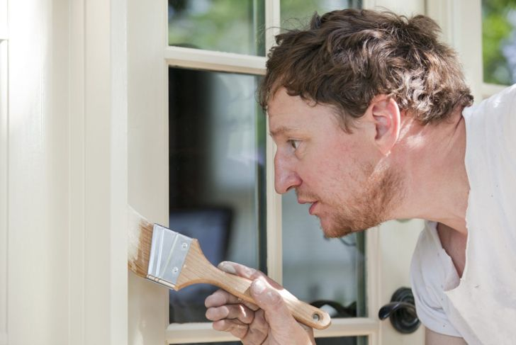 Man painting door frame