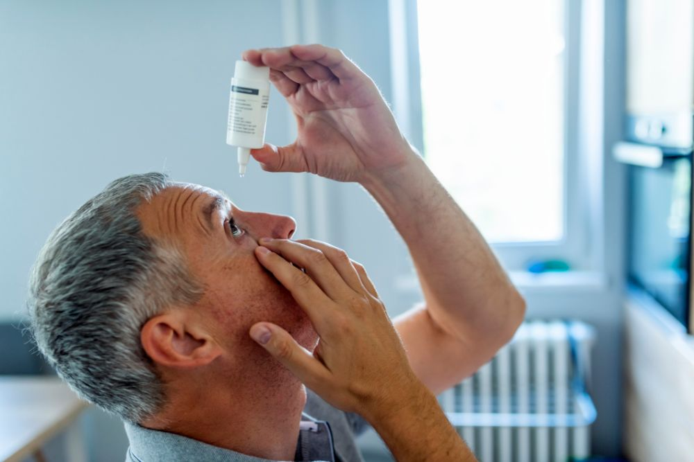 A man with grey hair putting eye drops in his eye