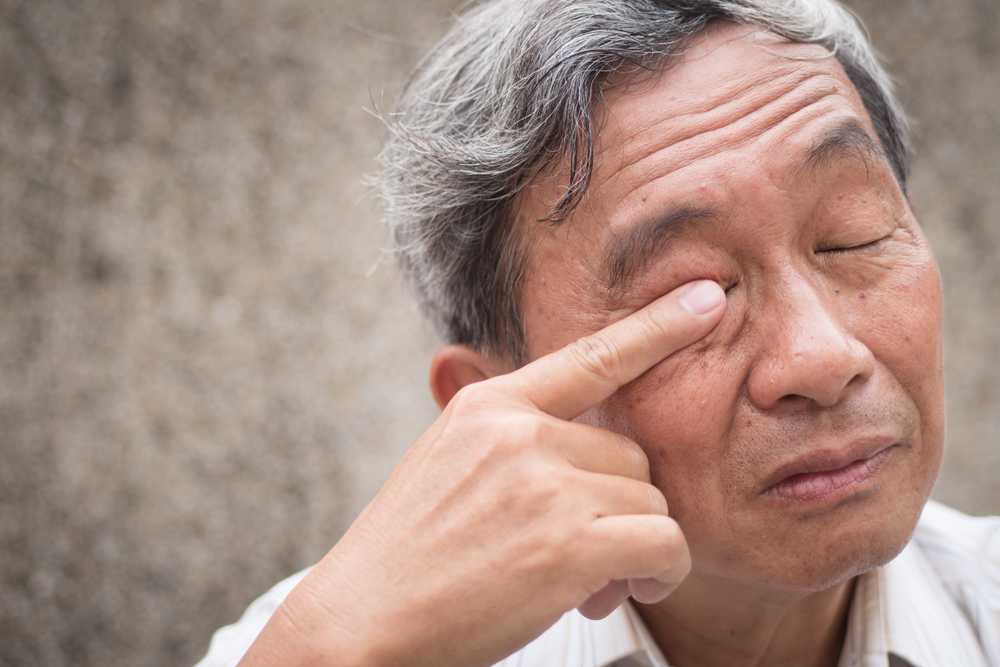 Man rubs right eye due to eye infection