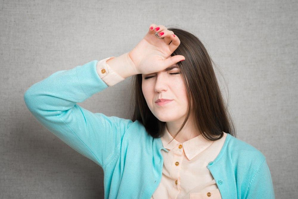 women in a blue sweater feeling her forehead