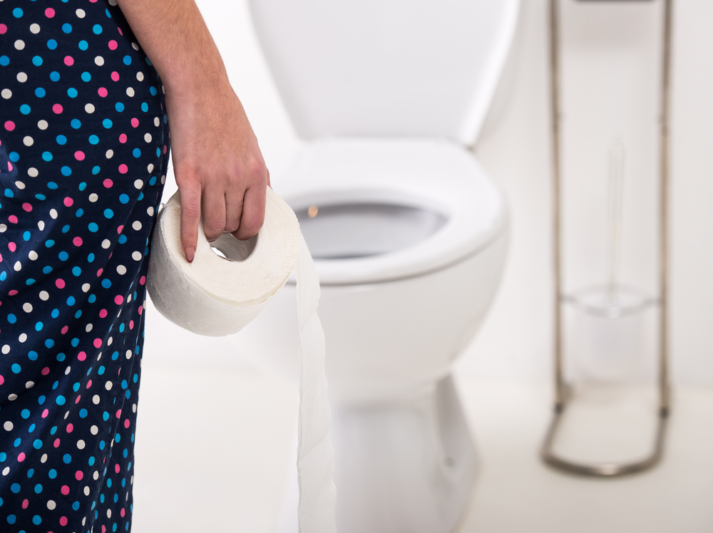 person holding toilet paper in front of toilet