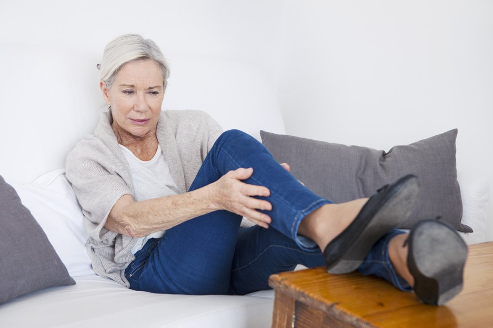 older women sitting on her couch holding her calf