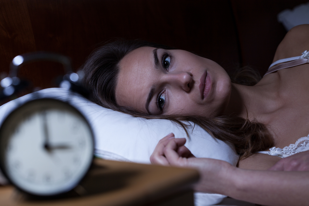 woman in bed watching the clock