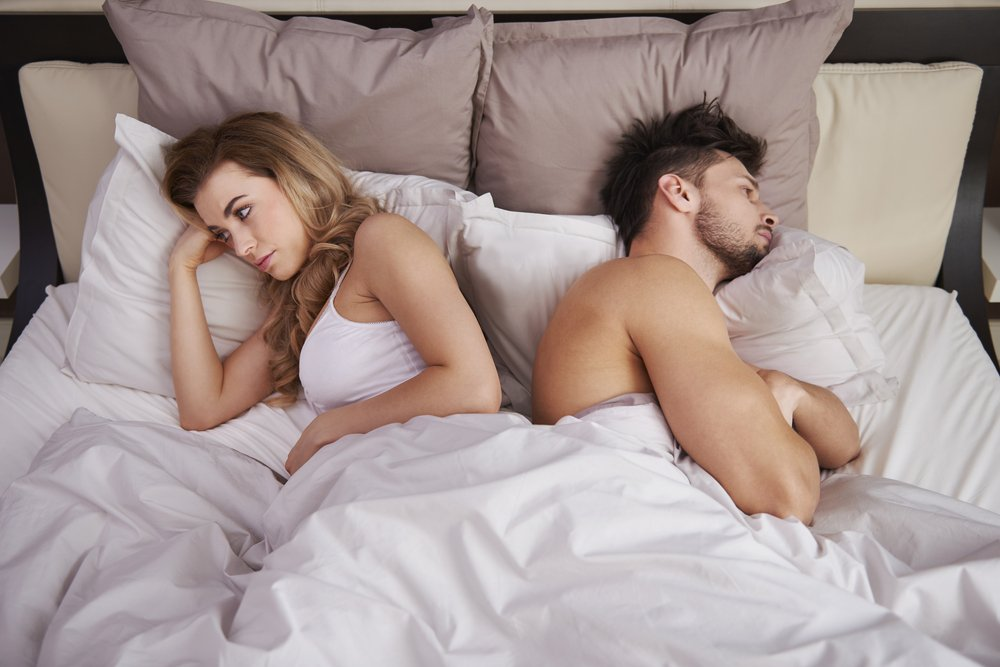 woman and man in bed facing away from each other
