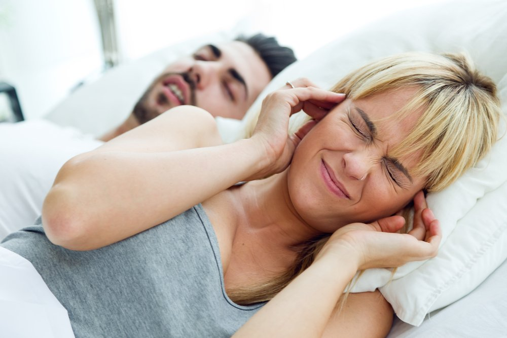 woman plugging her ears beside snoring husband