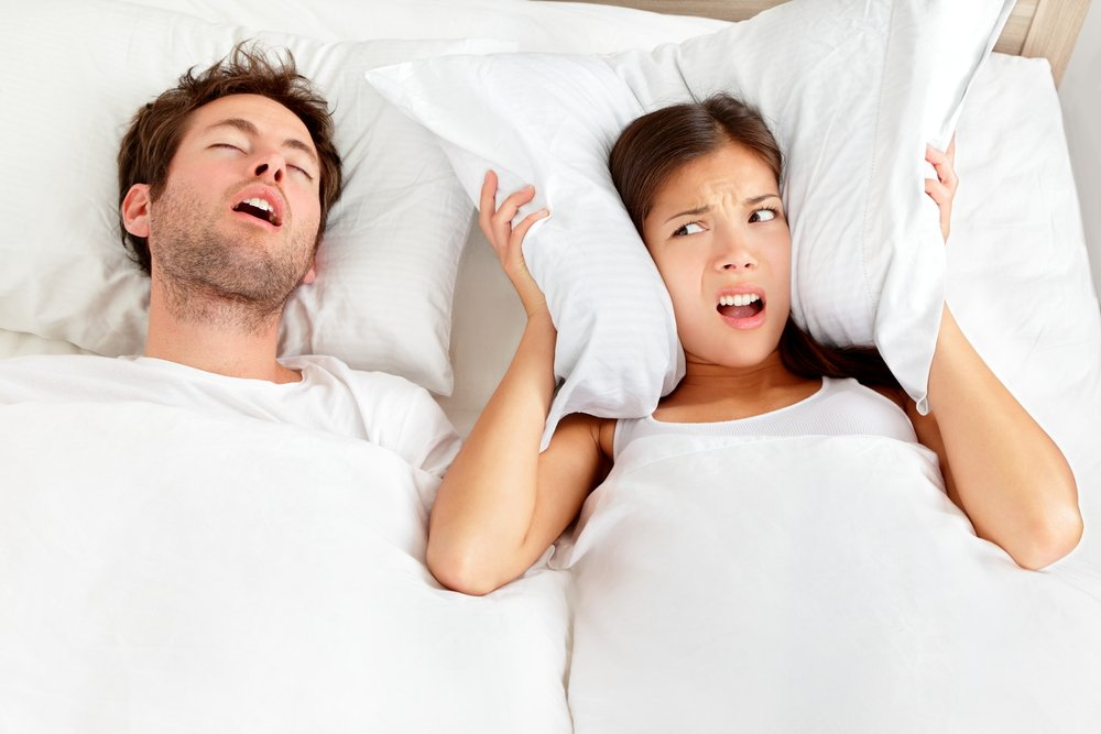 man snoring in bed beside his wife