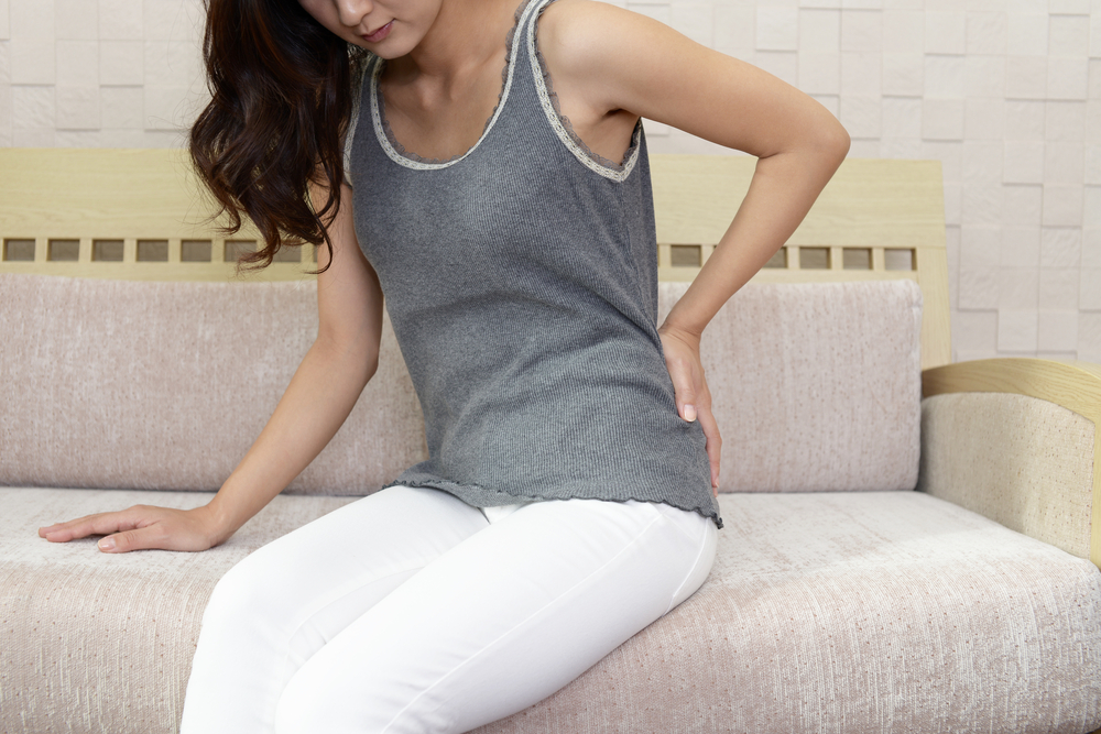 Woman sitting on a couch with her hand on her lower back