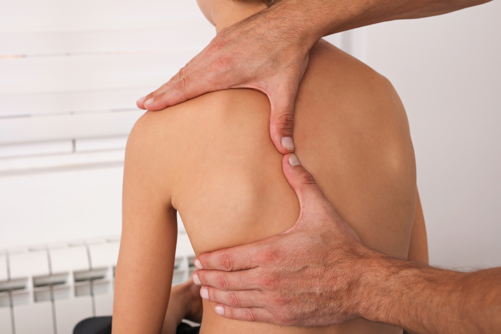 doctor checking shoulder alignment in young patient