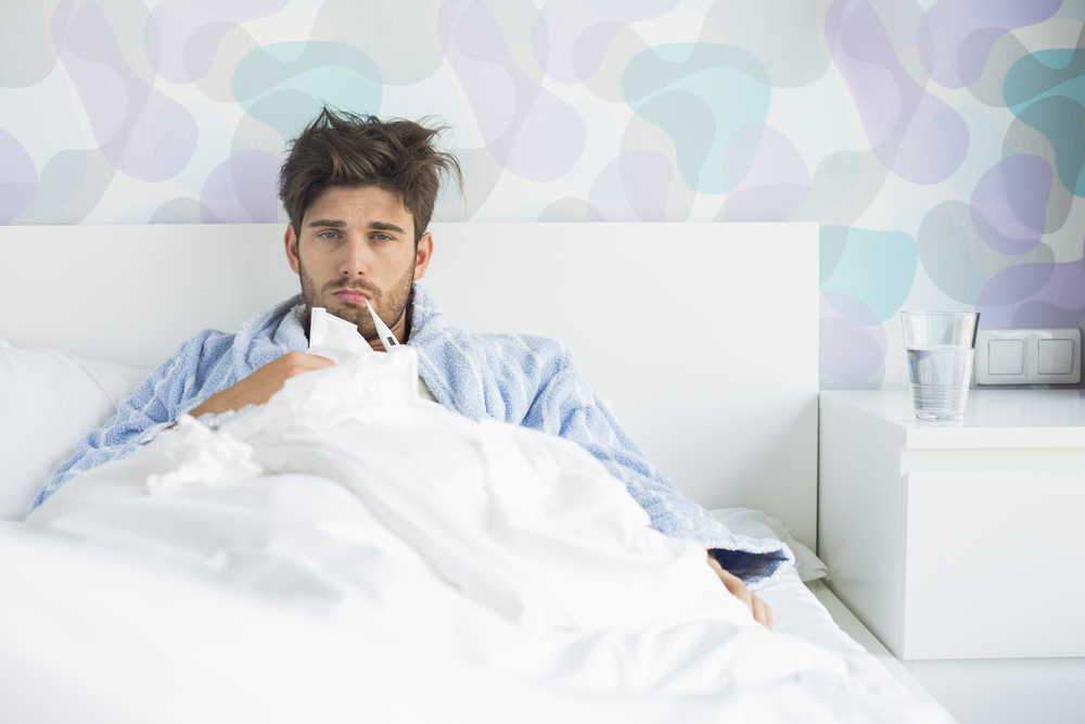 Man sitting in bed in a robe with a fever