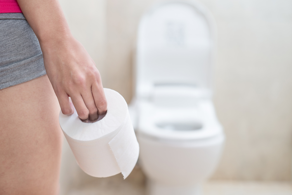 person in front of a toilet with toilet paper in hand due to diarrhea