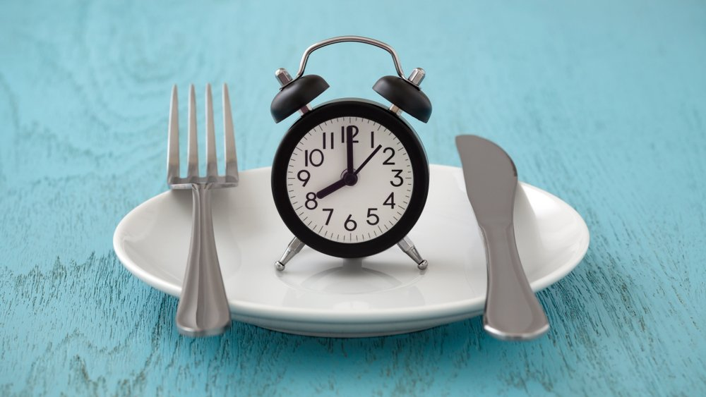 Fork and knife on plate with a black alarm clock in the middle