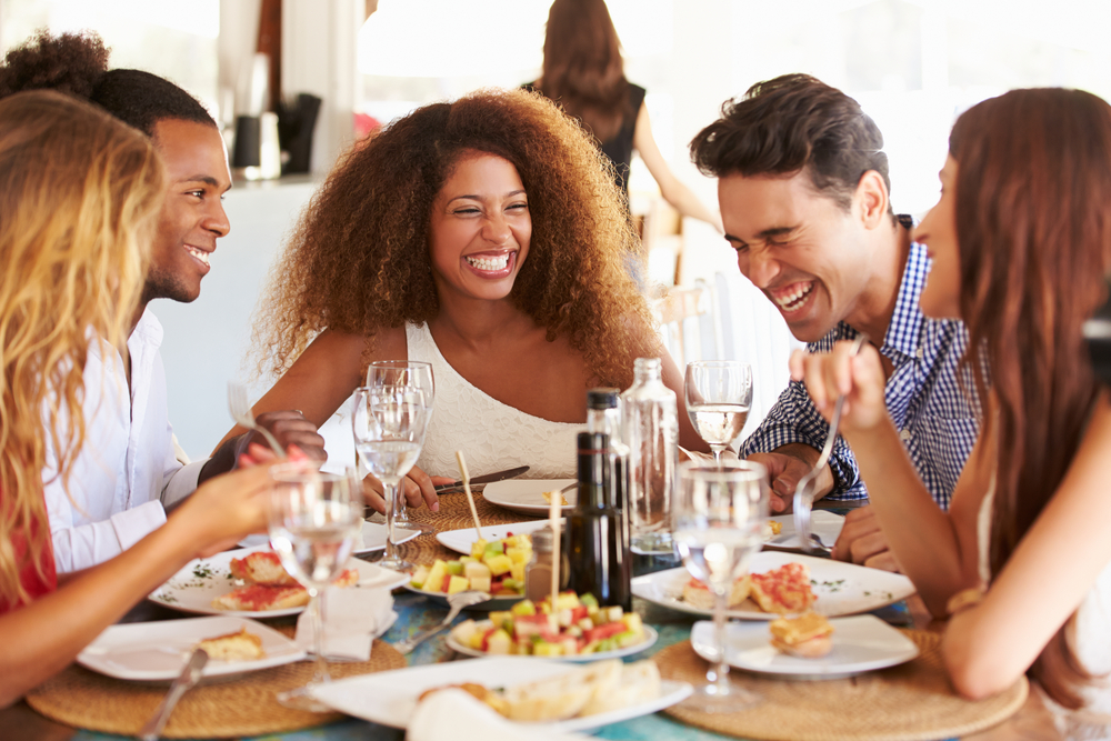 Three women and two men sit around a table of food smiling