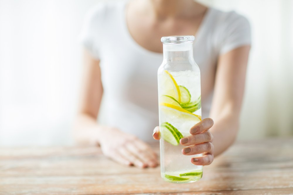 Hand holds bottle of water with sliced lemons and cucumbers inside