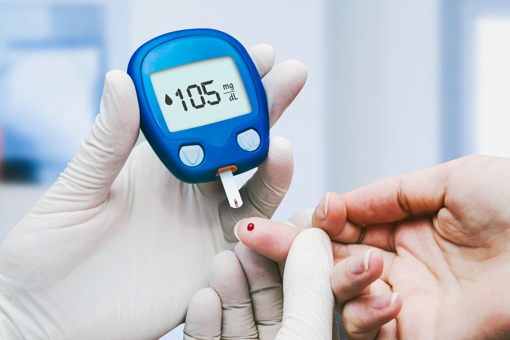 Gloved hand holds up another person's finger to a blood sugar reader
