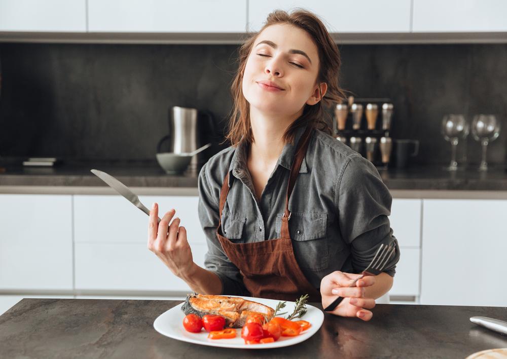 woman smiles while enjoying salmon and tomatoes