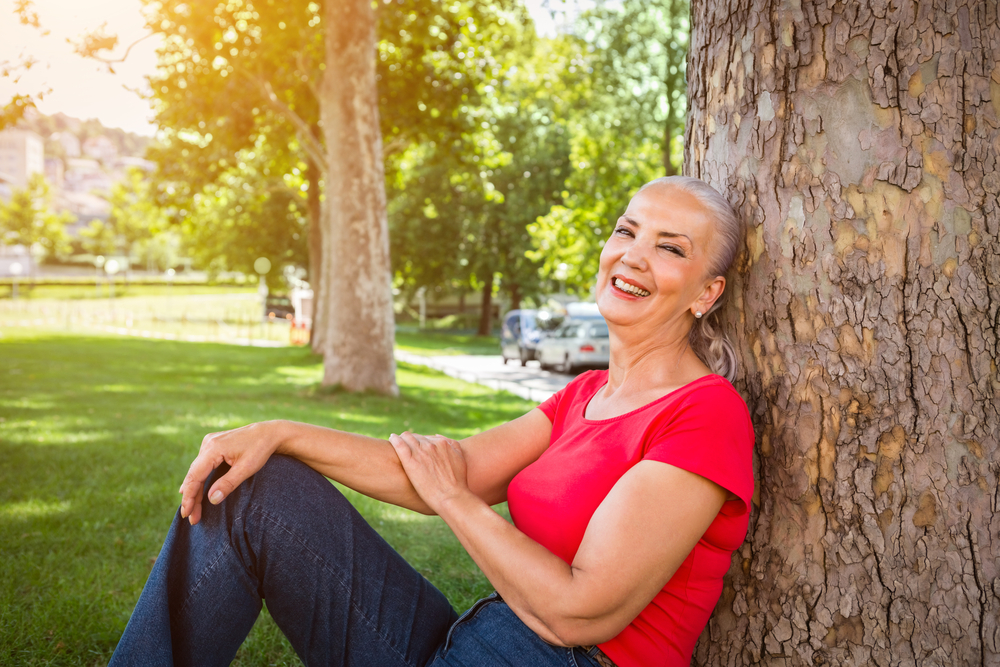 Older woman smiles while leaning against a tree