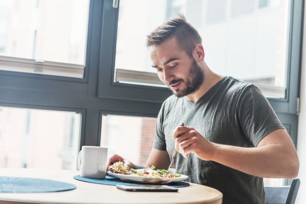 Man digs fork into a plate of food beside a sunlit window