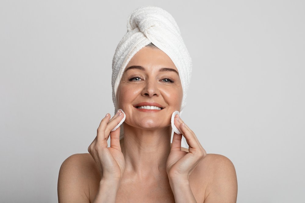 Beautiful mature lady with towel on head cleaning her face with lotion and cotton pads