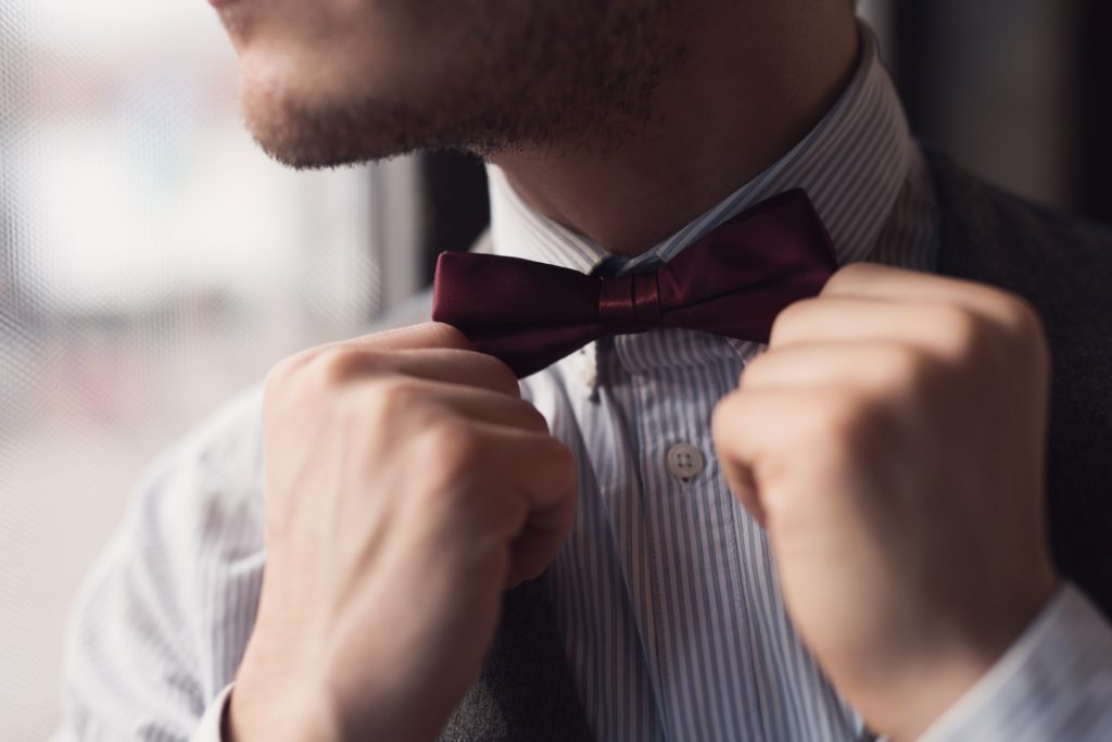 Close-up of an elegant man fixing his bow tie.
