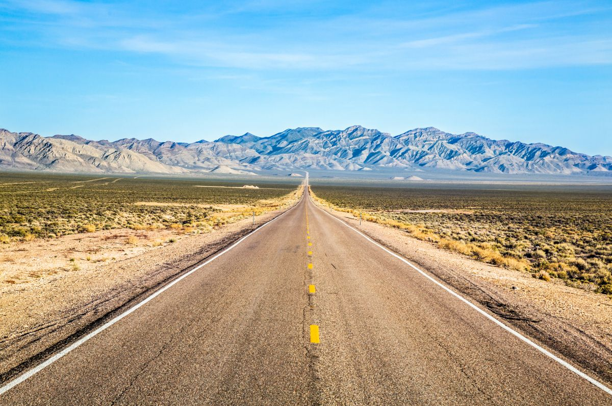 Wide open road and distant mountains in wide open Nevada desert along the Extraterrestrial Highway.