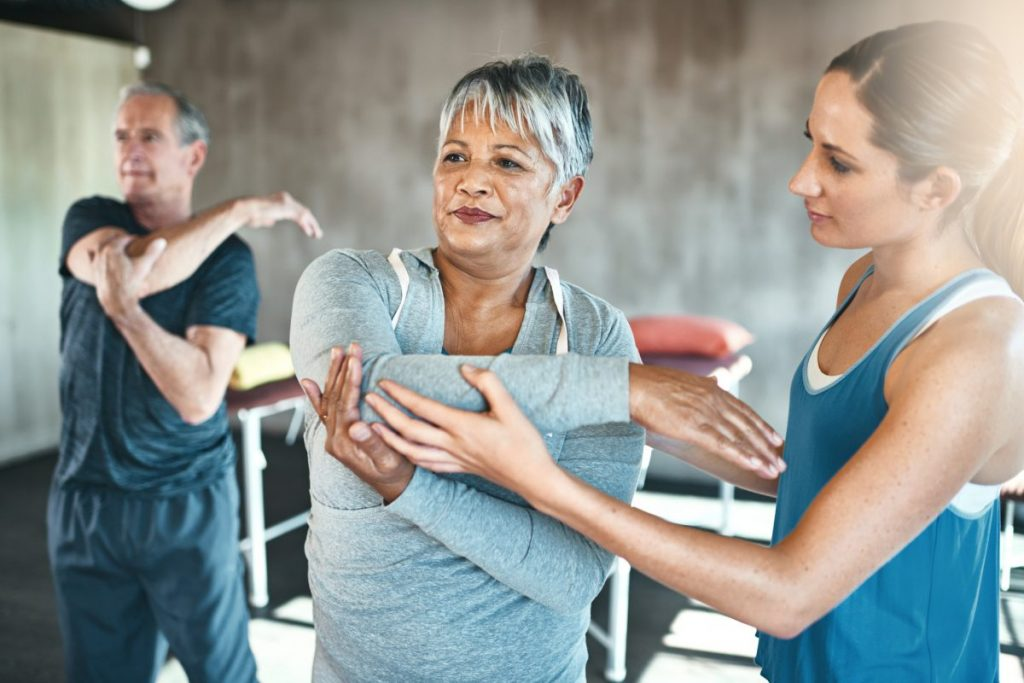 older people exercising stretching