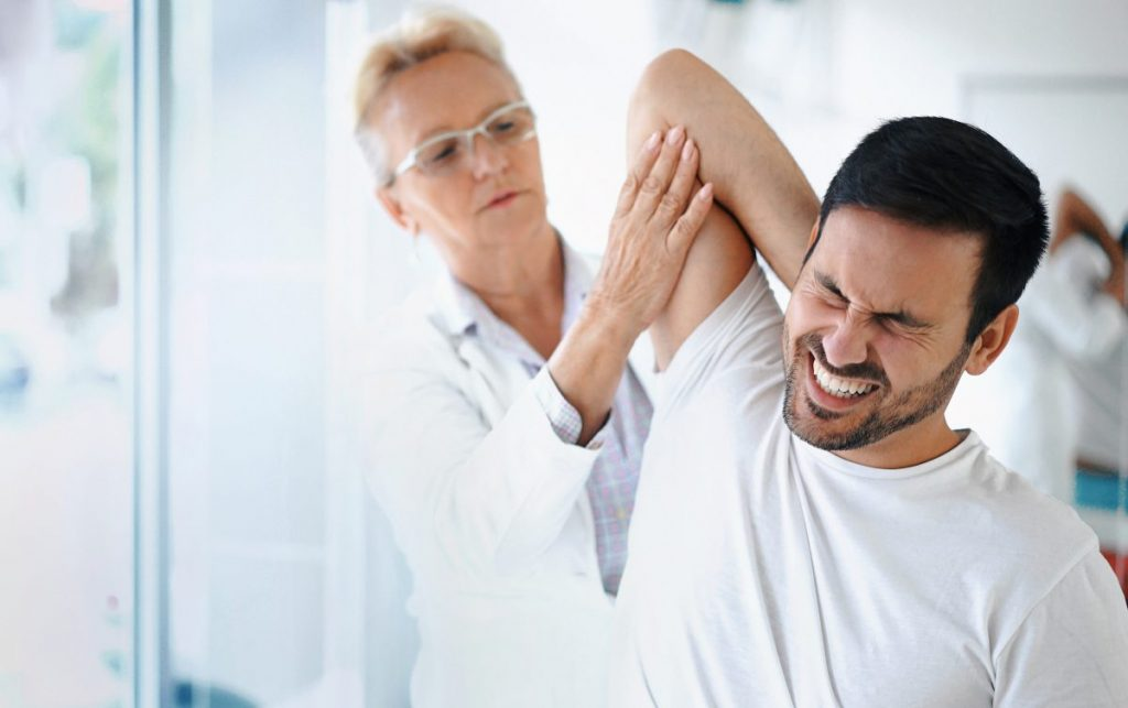 a doctor examines man's shoulder
