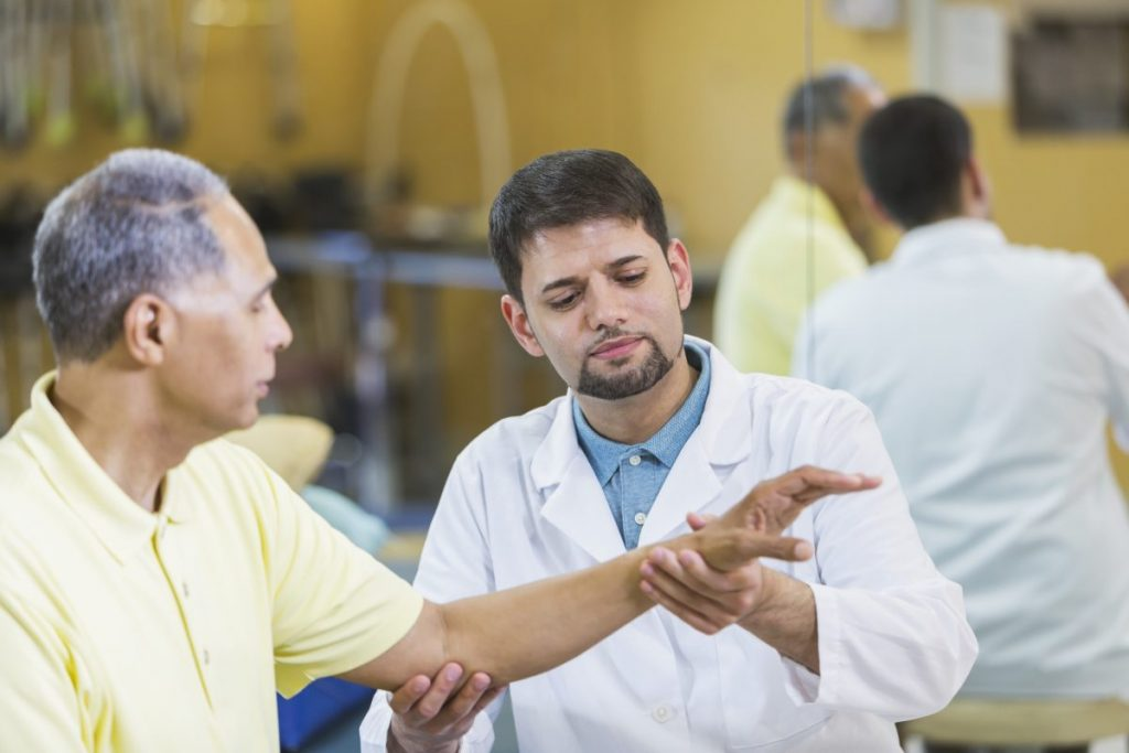 physical therapist checking patient wrist