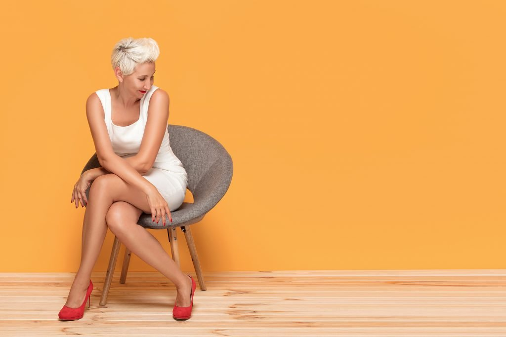 Beautiful middle aged blonde lady smiling, relaxing. Woman wearing red fashionable high heels posing on yellow studio background.