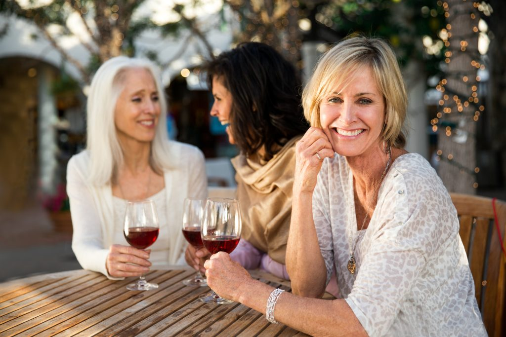 Three Beautiful, mature women drinking wine while taking at a table in a cafe outdoors. Its their girls night out. Women are chatting, laughing and having a great time. One of the woman is in main focus and looking at the camera with a warm smile. Women are between 50 and 65 years old.