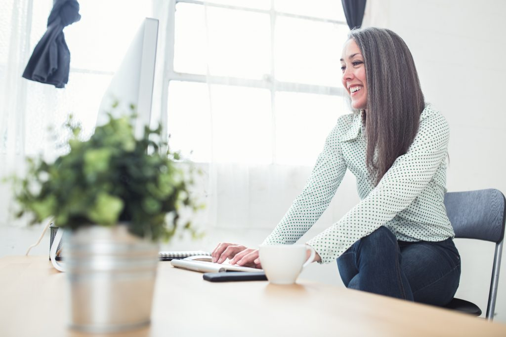 A female business woman in her 50's works at her desk in the office of her online business startup. Clean modern industrial work place environment with bright large windows. Horizontal image.