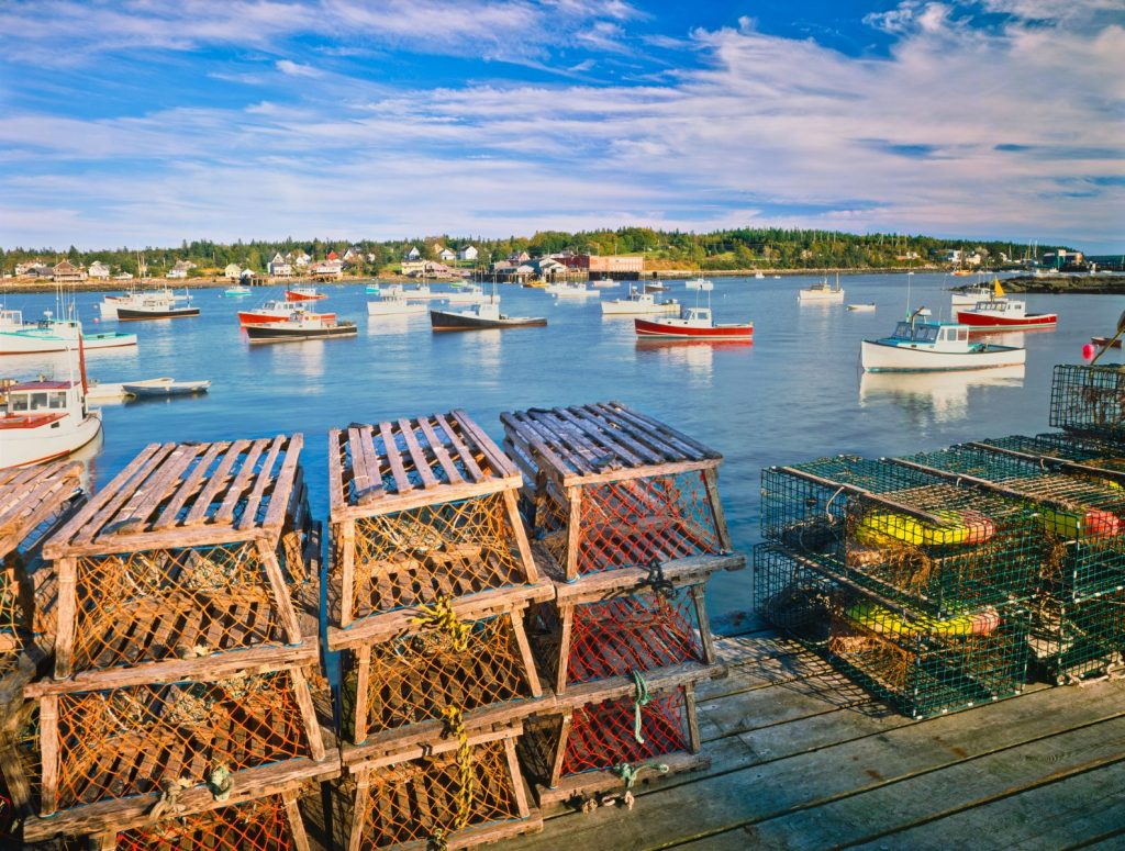 Wooden Lobster Traps On A Dock With Fishing Boats In Bernard At Bass Harbor Maine