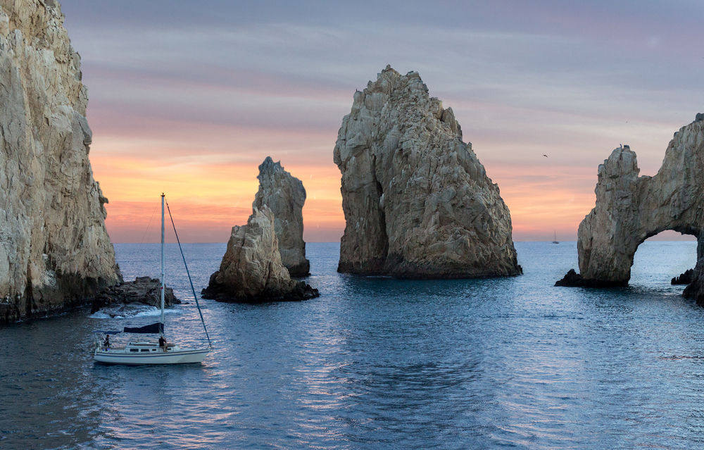 Beautiful Dramatic Seascape view of the ocean with colorful sunset and sailboats - Cabo san Lucas, Mexico