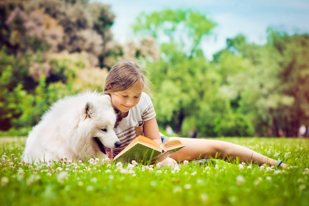 Girl and dog looking at book