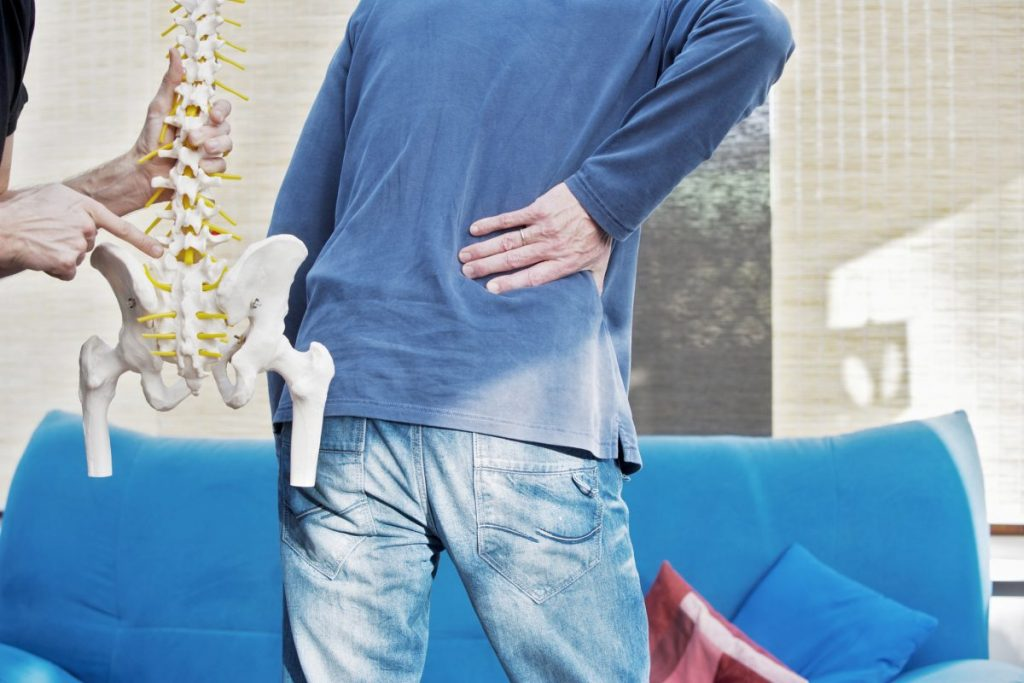 man holding his back with a fake spine beside him