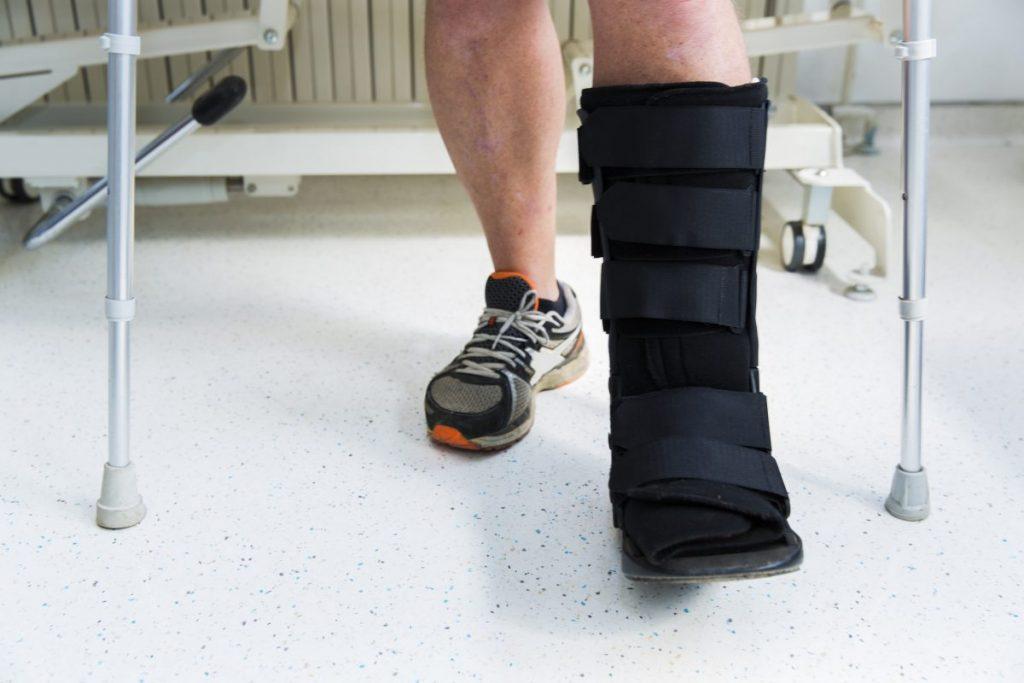 leg closeup in black cast with crutches