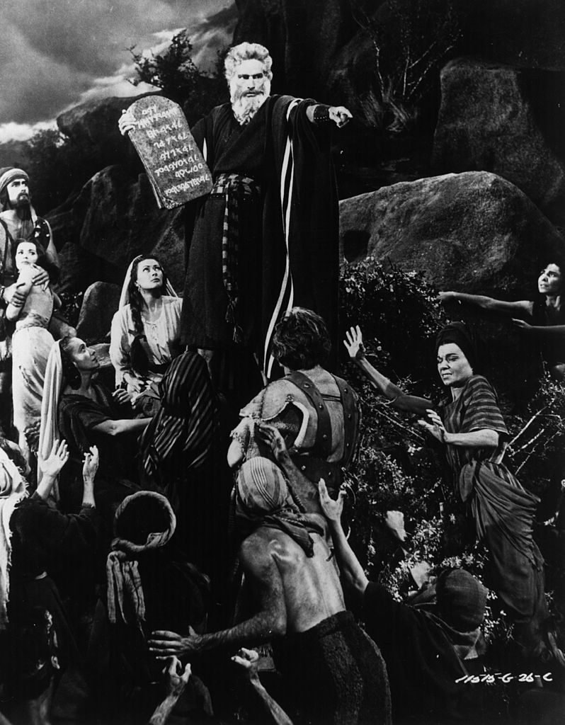 Moses, played by Charlton Heston, descends from Mount Sinai carrying the ten commandments to berate the worshippers of the golden calf, in the remake of the film, 'The Ten Commandments', directed by Cecil B DeMille.