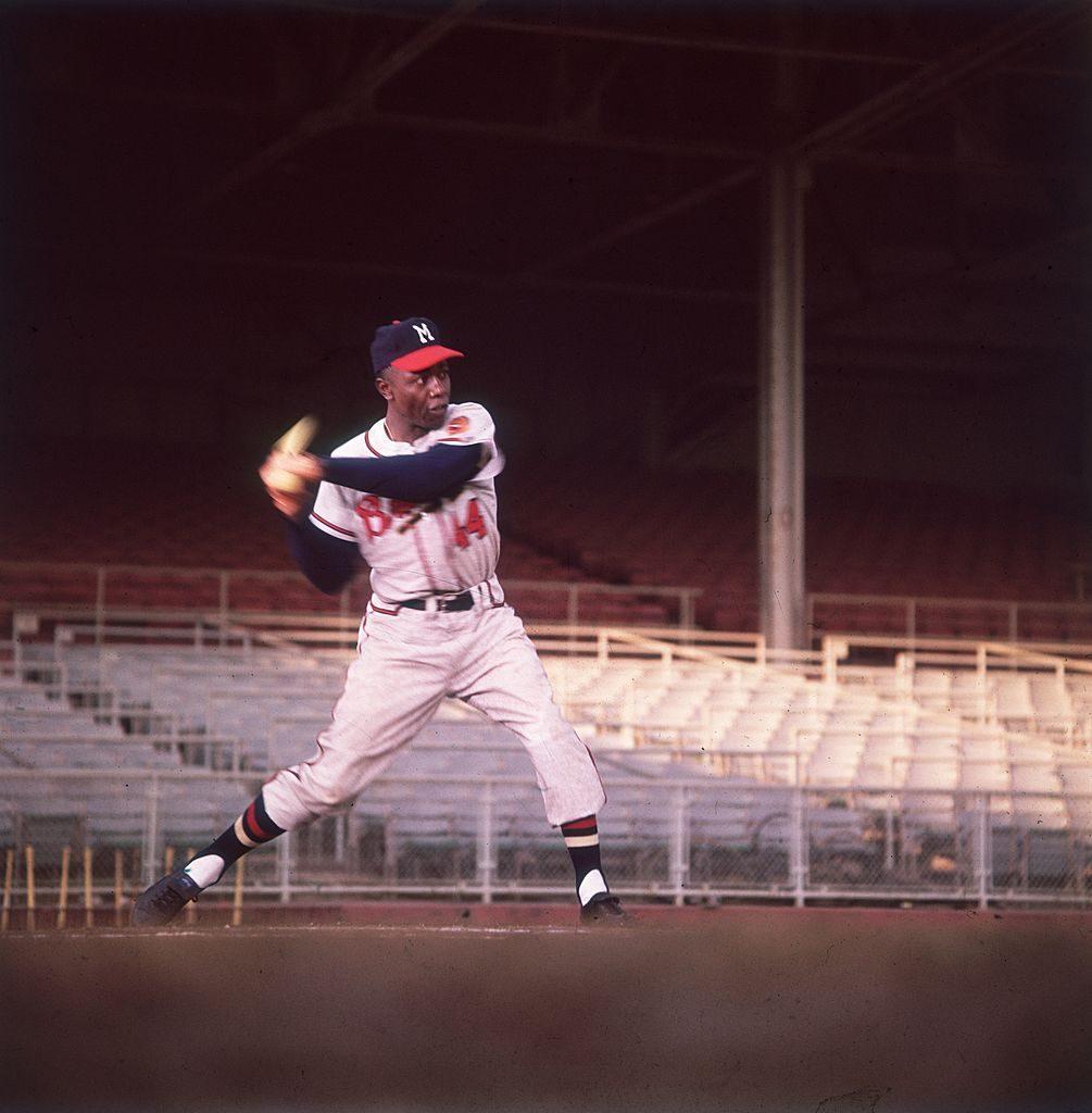 American baseball player Hank Aaron swings a bat in an empty stadium.