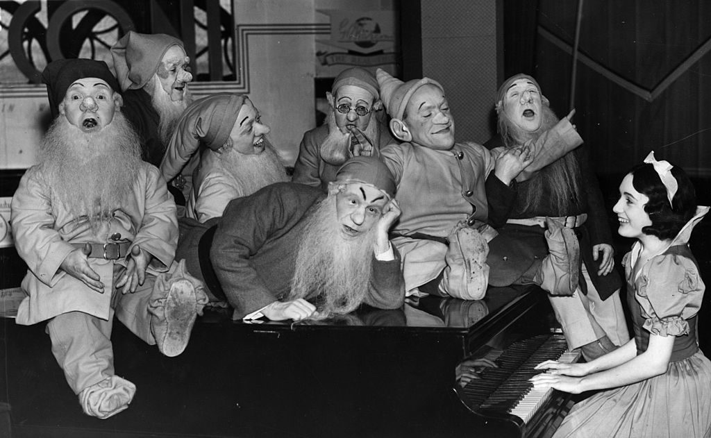 A group of actors dressed as Snow White and the Seven Dwarves entertain the Christmas shoppers at a store in London's Clapham Junction.