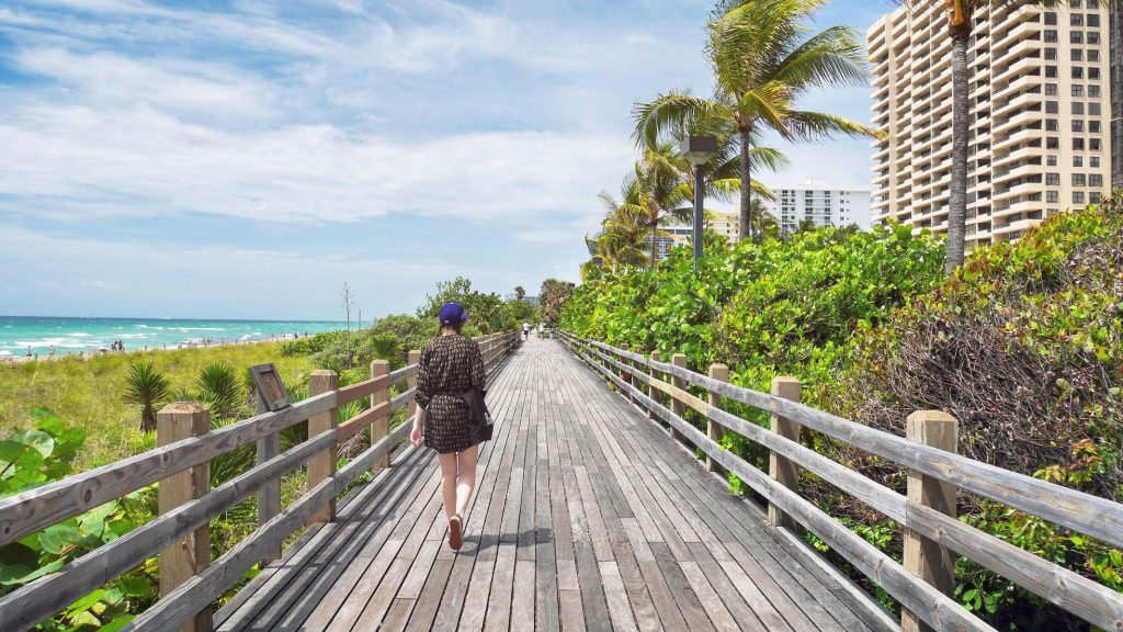 a girl walking on the boardwalk in Miami