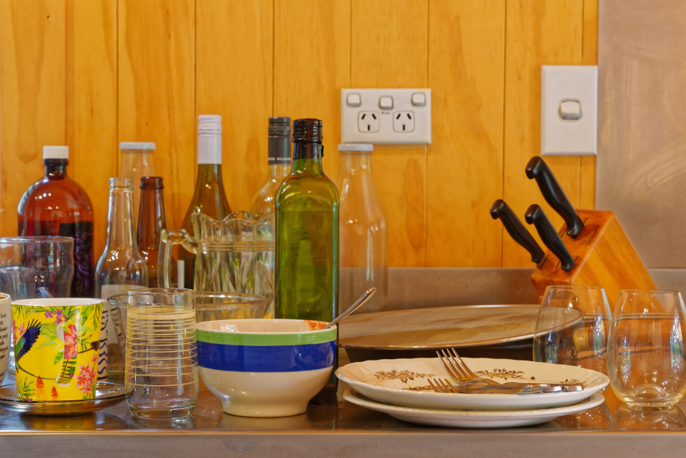 Dirty dishes and bottles piled on a stainless steel sink.