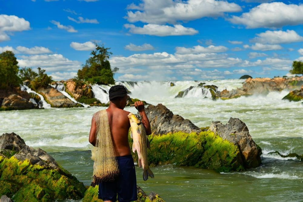 Khone Phapheng Falls and fisherman on beautiful sky, Laos