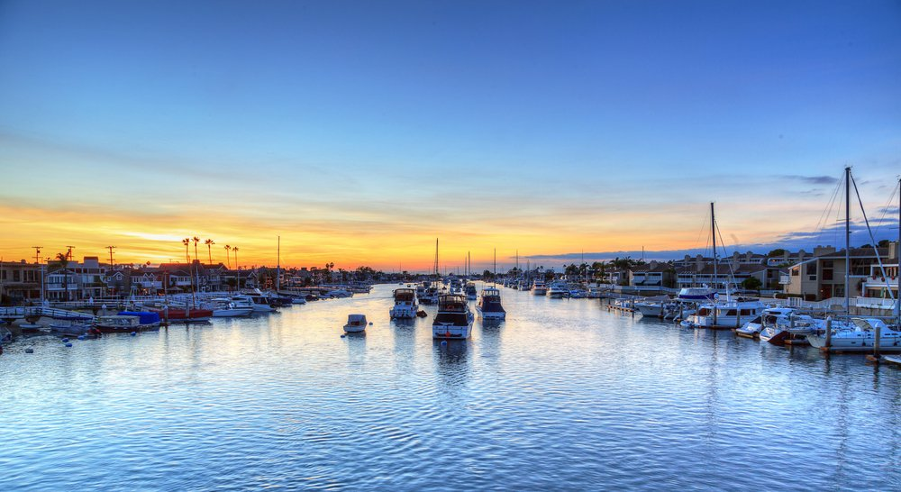Balboa Island harbor at sunset with ships and sailboats visible from the bridge that leads into Balboa Island