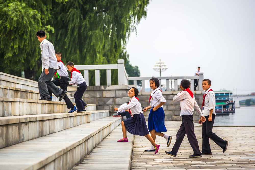 Young students walking around Pyongyang, capital of North Korea in cloudy day
