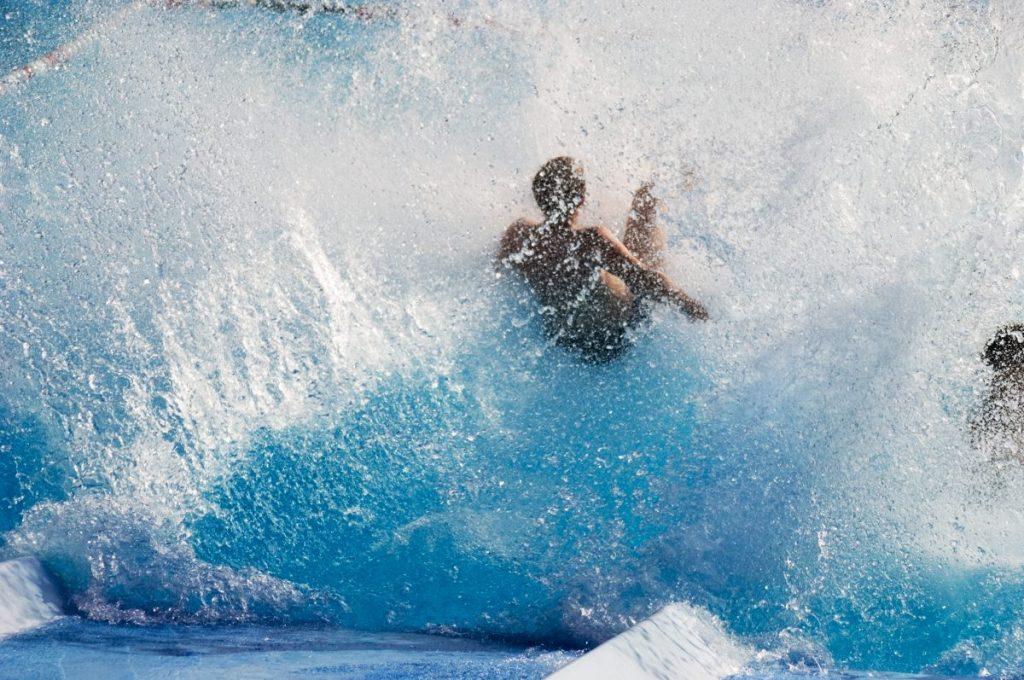Close-up of boy splashing into pool